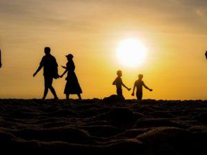 夕日と浜辺を歩くカップル